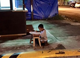 Filipino boy receives scholarship after photograph of him studying goes viral